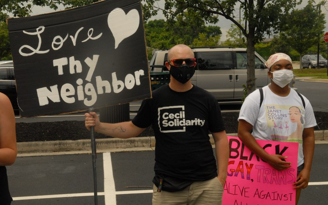 Protestor with Love Thy Neighbor on sign