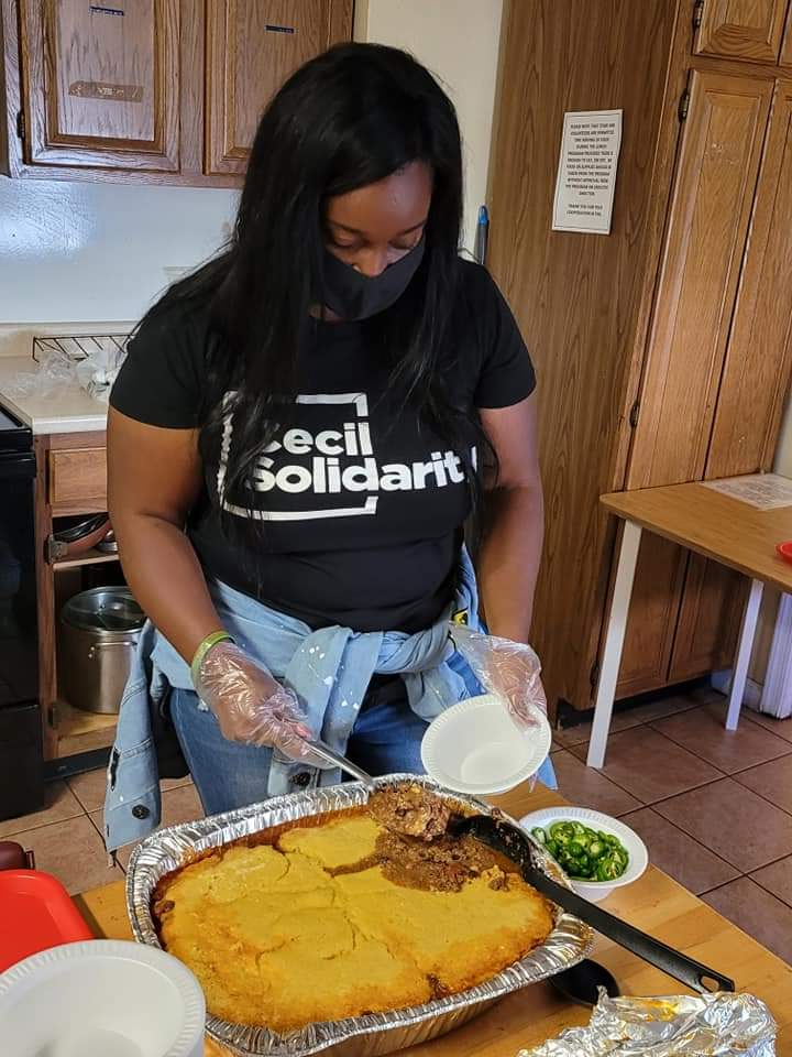 President Christine Givens serves food at Meeting Ground