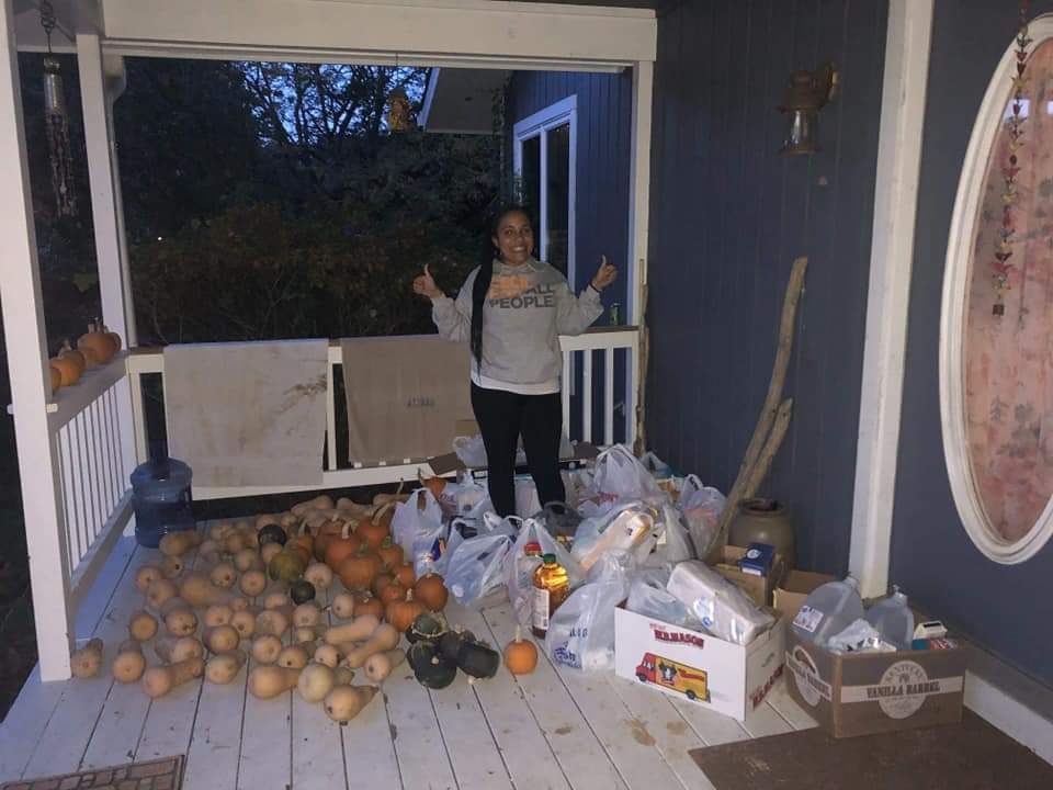 Volunteer Beth An Griffin poses with a porch full of donated food