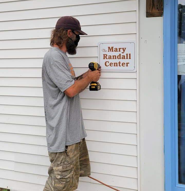 Volunteer Nick Letts hangs a sign